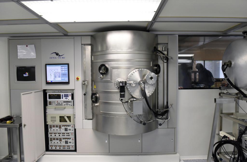 Vue d'une machine de dépôt commerciale par pulvérisation par faisceau d'ions. Cette machine peut traiter 6 pièces de 50 mm de diamètre en même temps